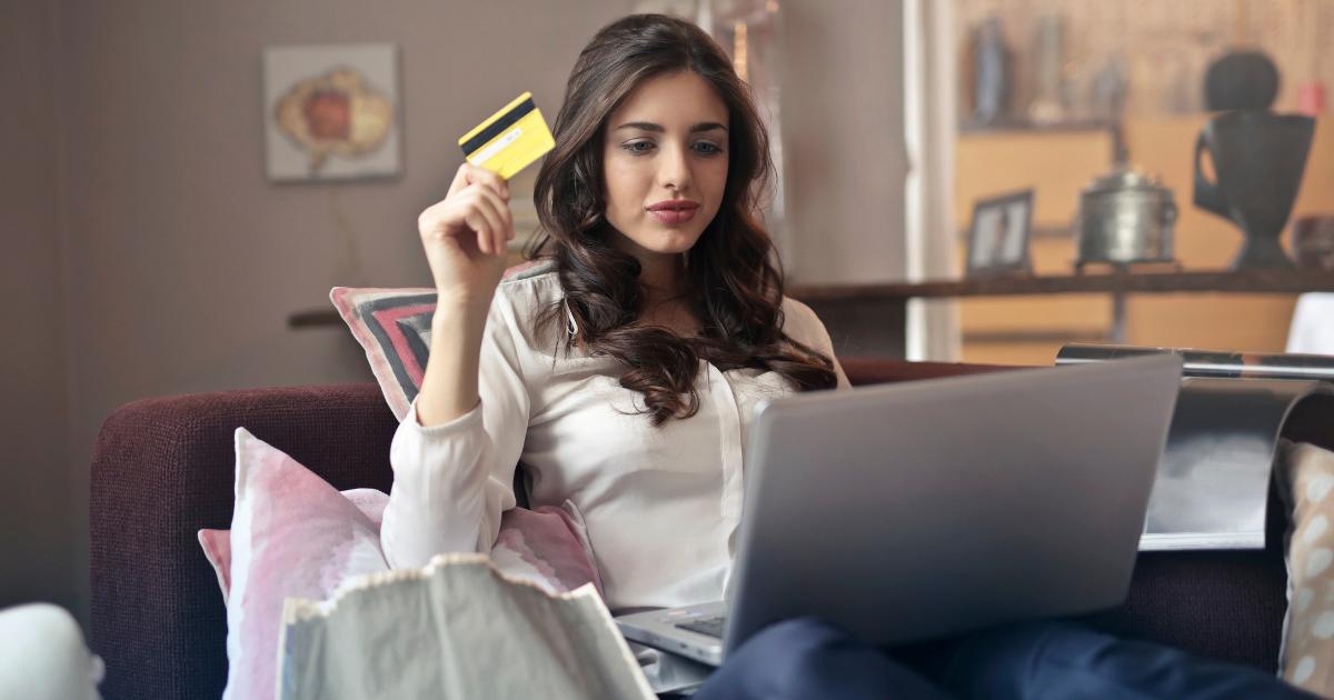 クレジットカード持ちながらパソコンをする女性