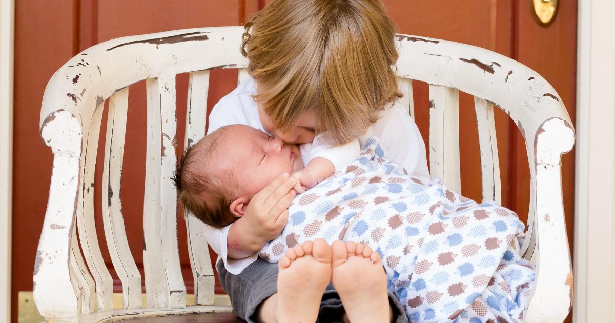 赤ちゃんを抱いて座っている女の子