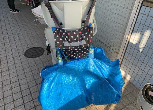 電動自転車の後ろにひっかけられたお昼寝布団が入ったIKEAのショッピングバッグ
